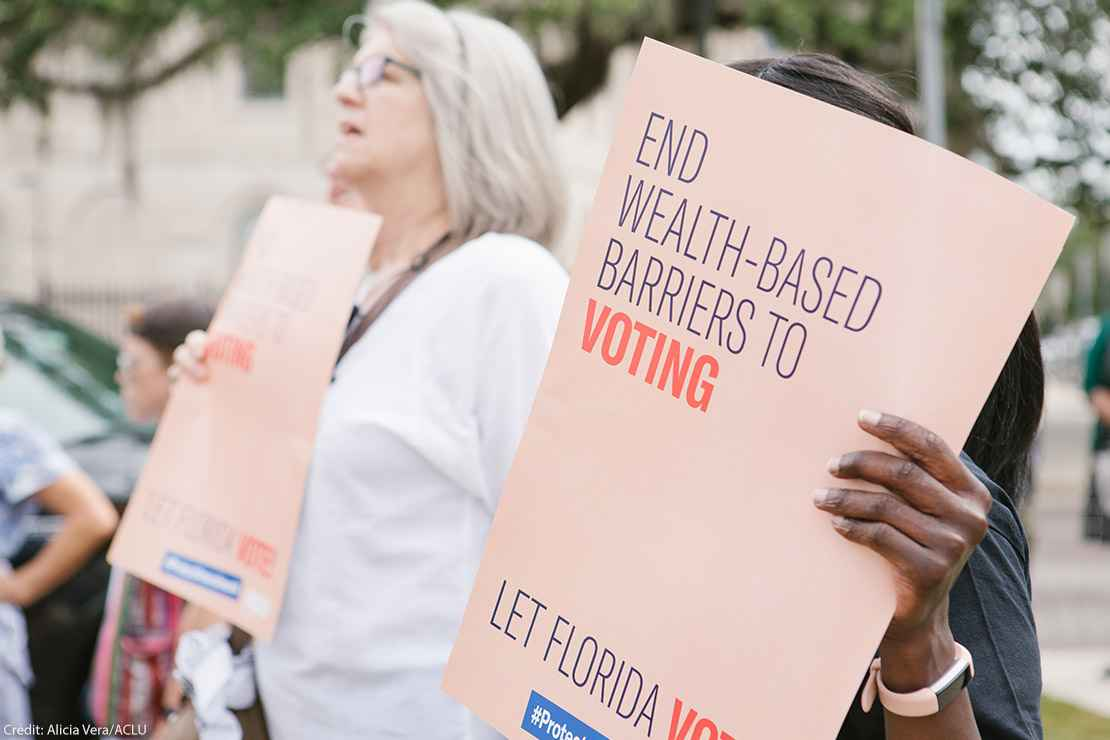 Woman holding sign reading 'End wealth based barriers to voting""