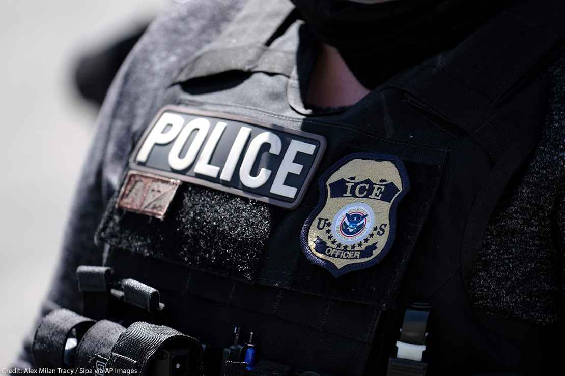 "A close up of a police officer wears a ""Police"" label beside a U.S. ICE (standing for Immigration and Customs Enforcement) badge on his vest."