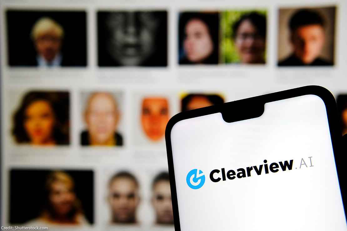 Clearview AI facial recognition software logo on the glowing screen and blurred faces from social media on the background
