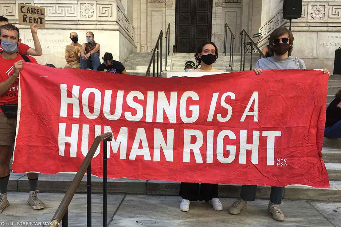 "Protesters carrying a banner with the text ""housing is a human right."