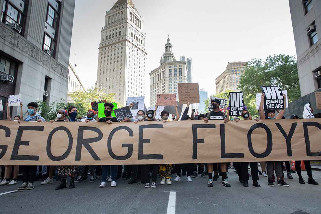 Black Lives Matter demonstrators marching with a large banner with George Floyd's name.