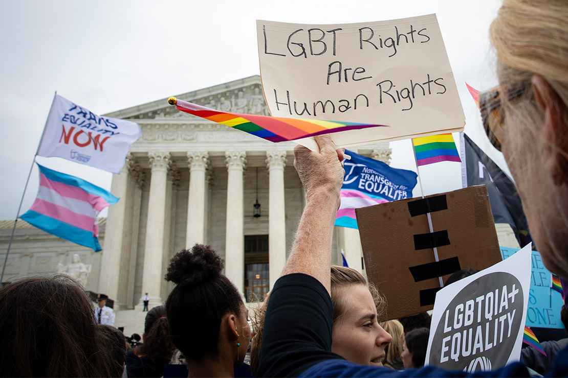 Demonstrators outside the Supreme Court with signs advocating for the rights of LGBT people.