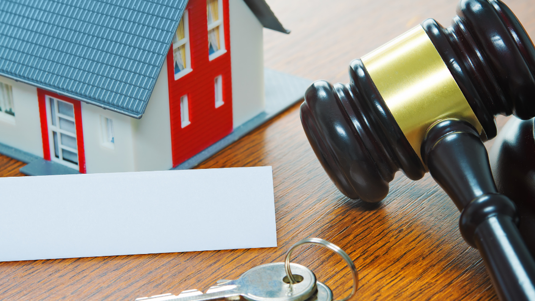left to right: a small toy house, a deed, two keys, and a gavel sitting on a wooden surface