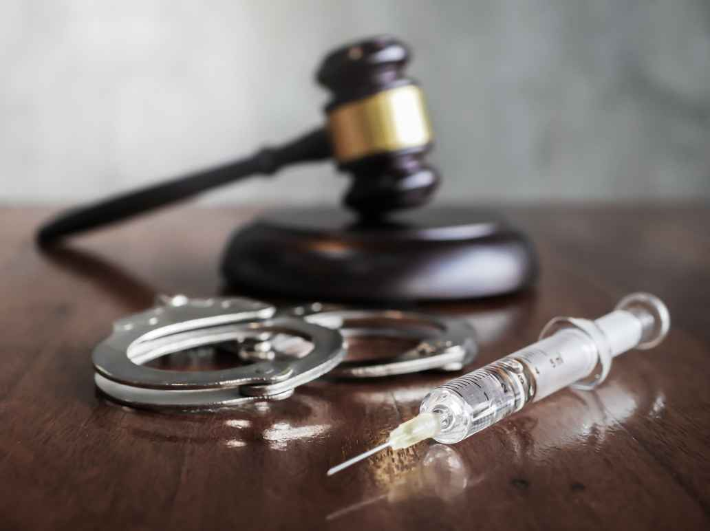 A gavel, a pair of handcuffs, and a syringe sitting on a desk.
