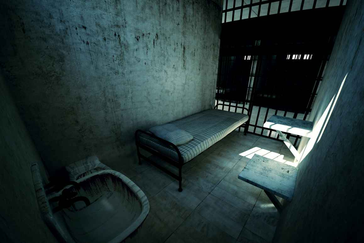 Dark prison cell with a bed and toilet